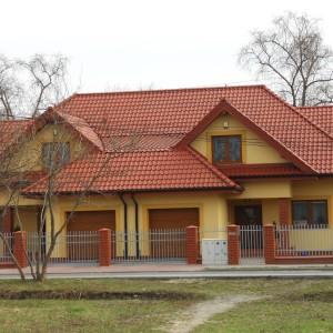 Dom jednorodzinny, stolarka PVC CT70 CAVA, kolor Złoty dąb, drzwi wejściowe PVC SCHÜCO, bramy garażowe KRISPOL